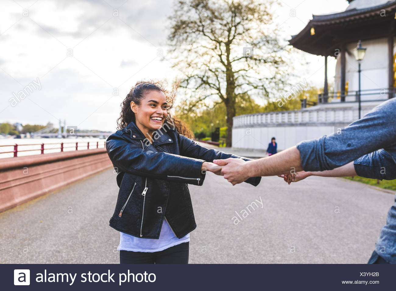 Young woman and boyfriend dancing and holding hands in Battersea Park - Stock Image