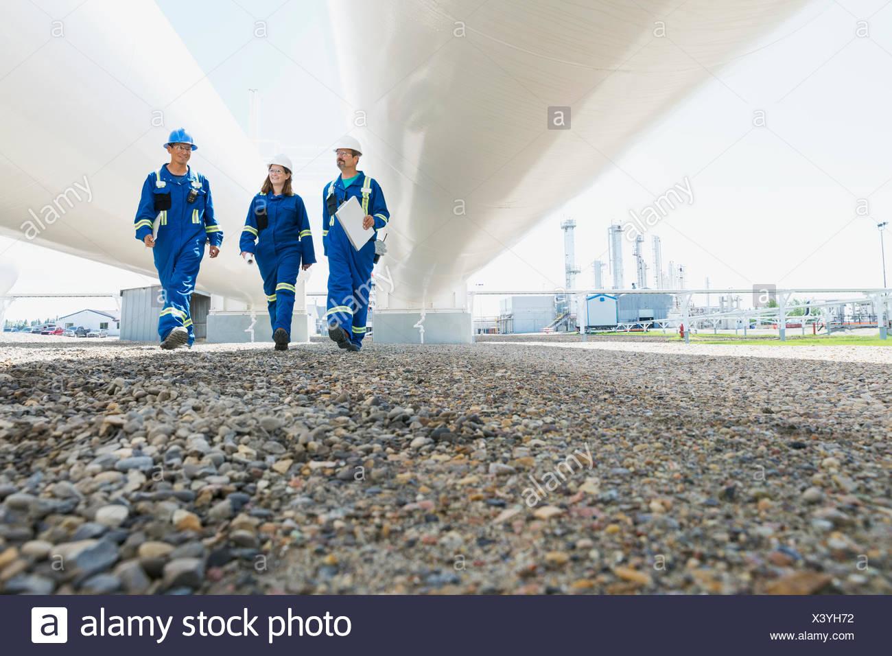 Workers walking below tanks at gas plant - Stock Image
