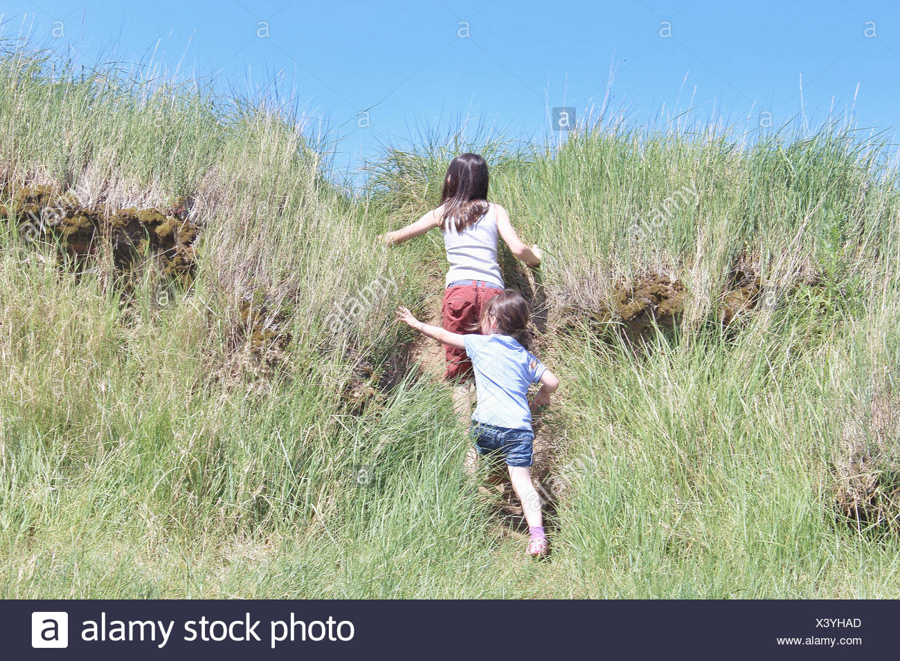 Rear view of two girls running up a hill - Stock Image
