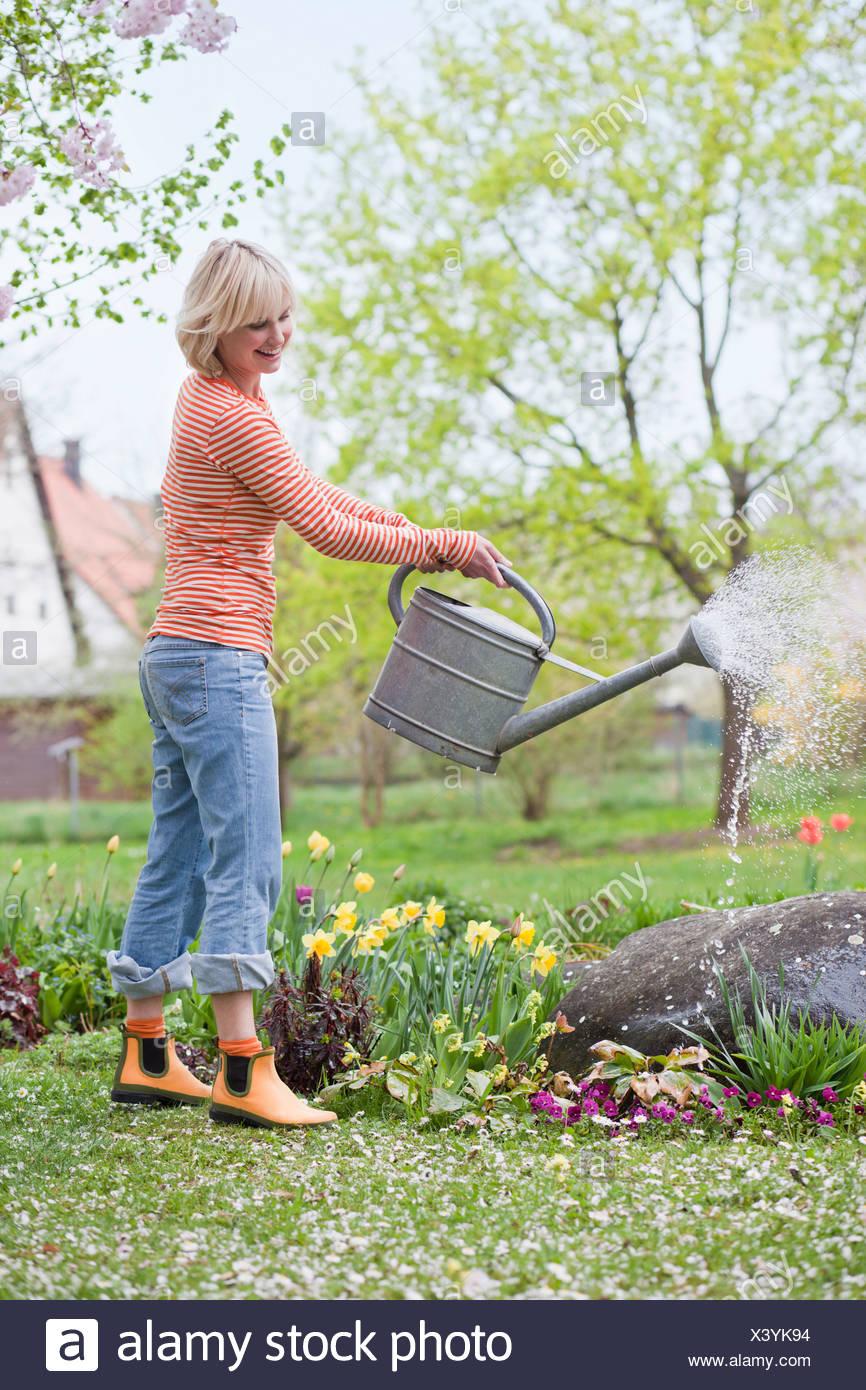 woman watering garden flowers - Stock Image