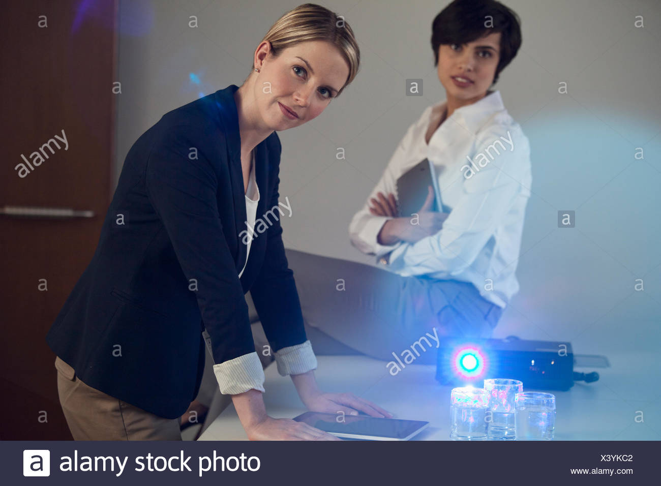 female coworkers using projector - Stock Image