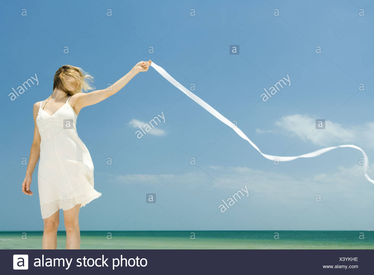Woman in sundress holding up ribbon in breeze, hair covering face - Stock Image