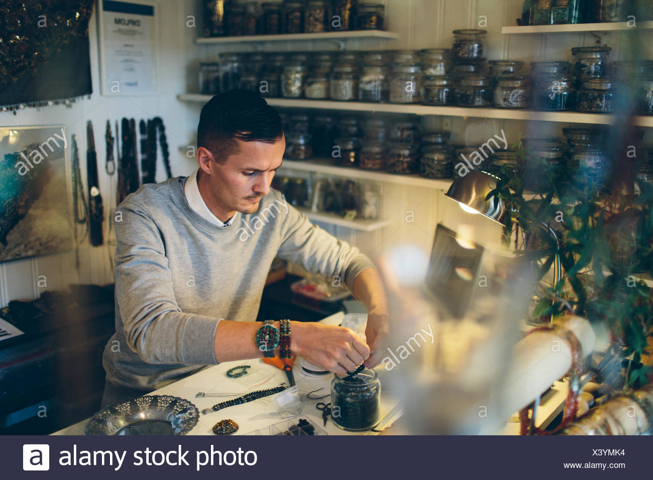 A man making beaded jewelry - Stock Image