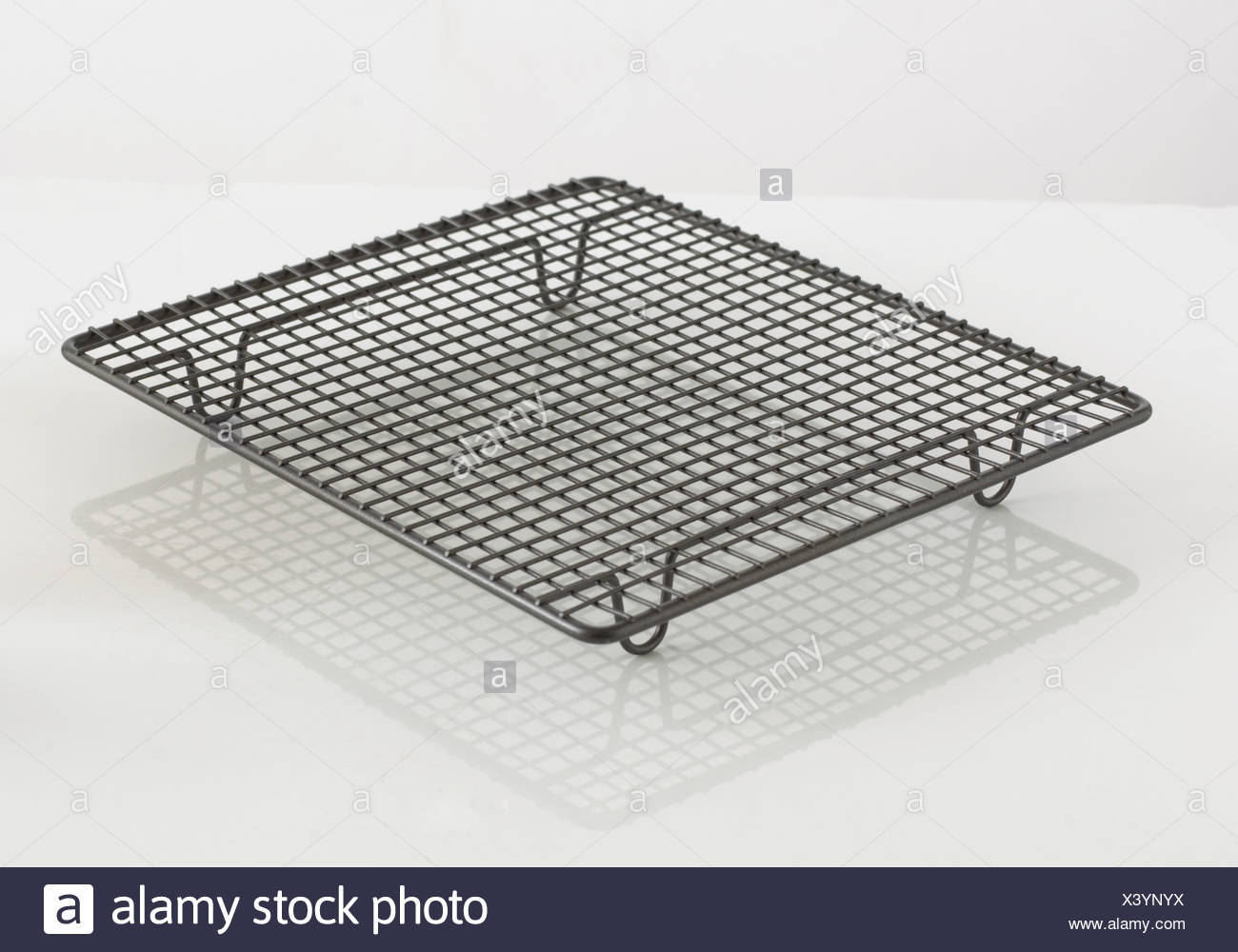 Wire cooling rack for baking on white background - Stock Image