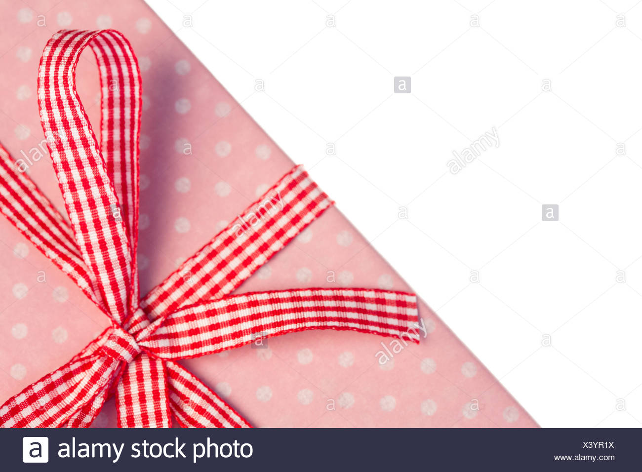 Pink gift wrapped present with gingham ribbon - Stock Image