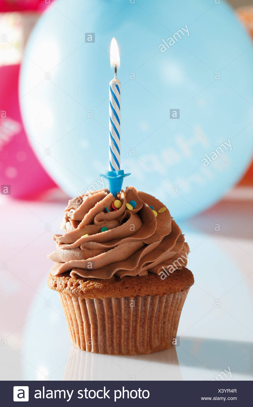 Close up of chocolate buttercream cupcake with birthday candle - Stock Image