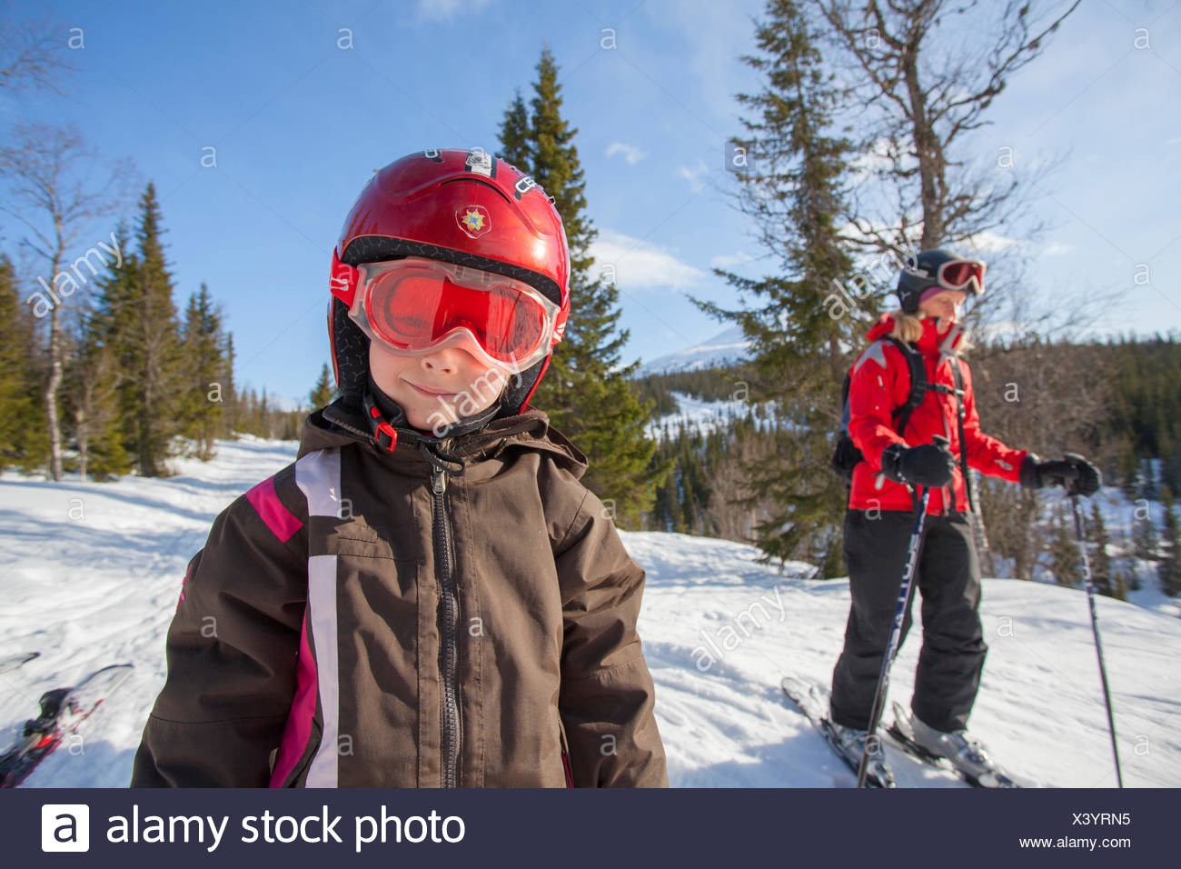 Norway, Osterdalen, Trysil, Portrait of smiling girl (4-5) standing on ski slope - Stock Image