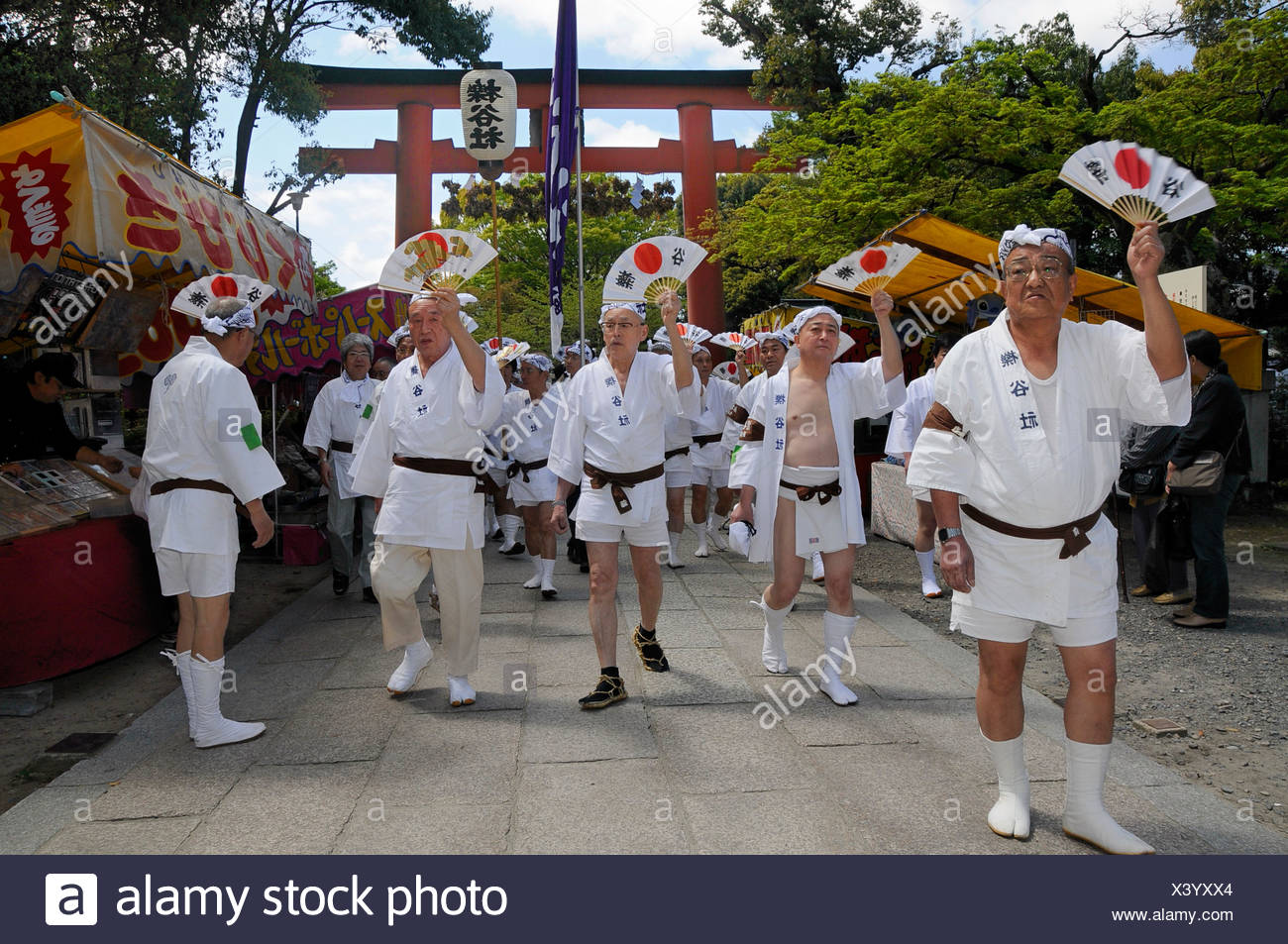 Handles of the shrines being carried accompanied by waving fans, Matsuri Shrine Festival of the Matsuo Taisha Shrine, Shinto Stock Photo