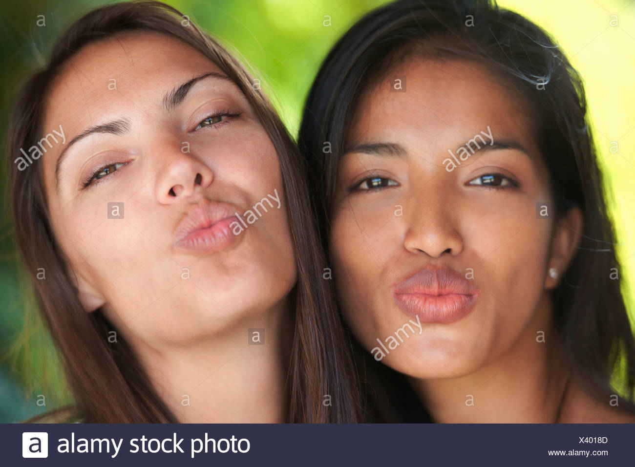 Close up portrait of two woman friends puckering lips - Stock Image