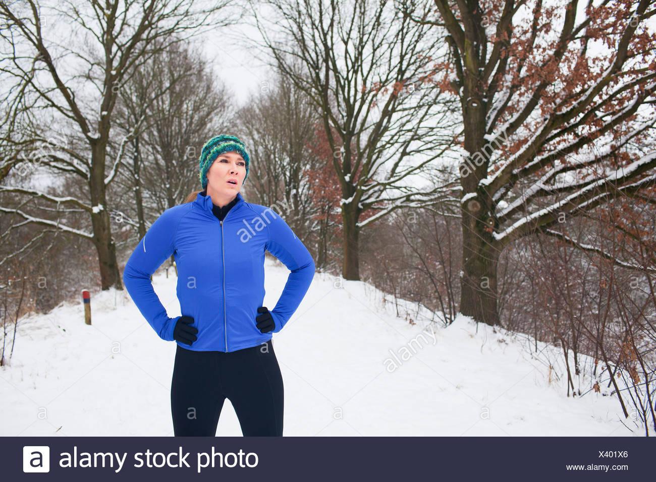 Female jogger taking a break in snow covered scene - Stock Image