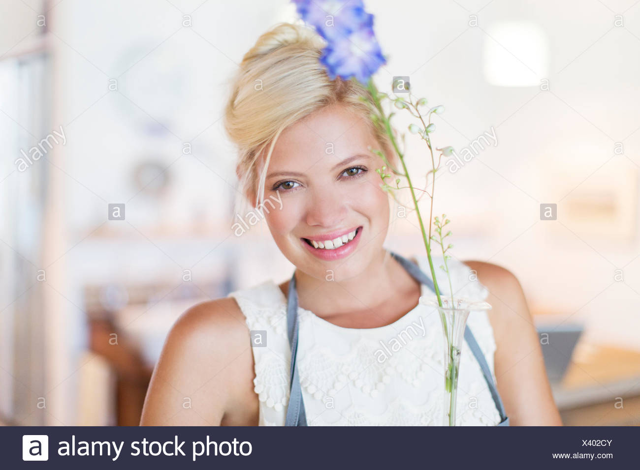 Woman holding flower in rustic kitchen - Stock Image