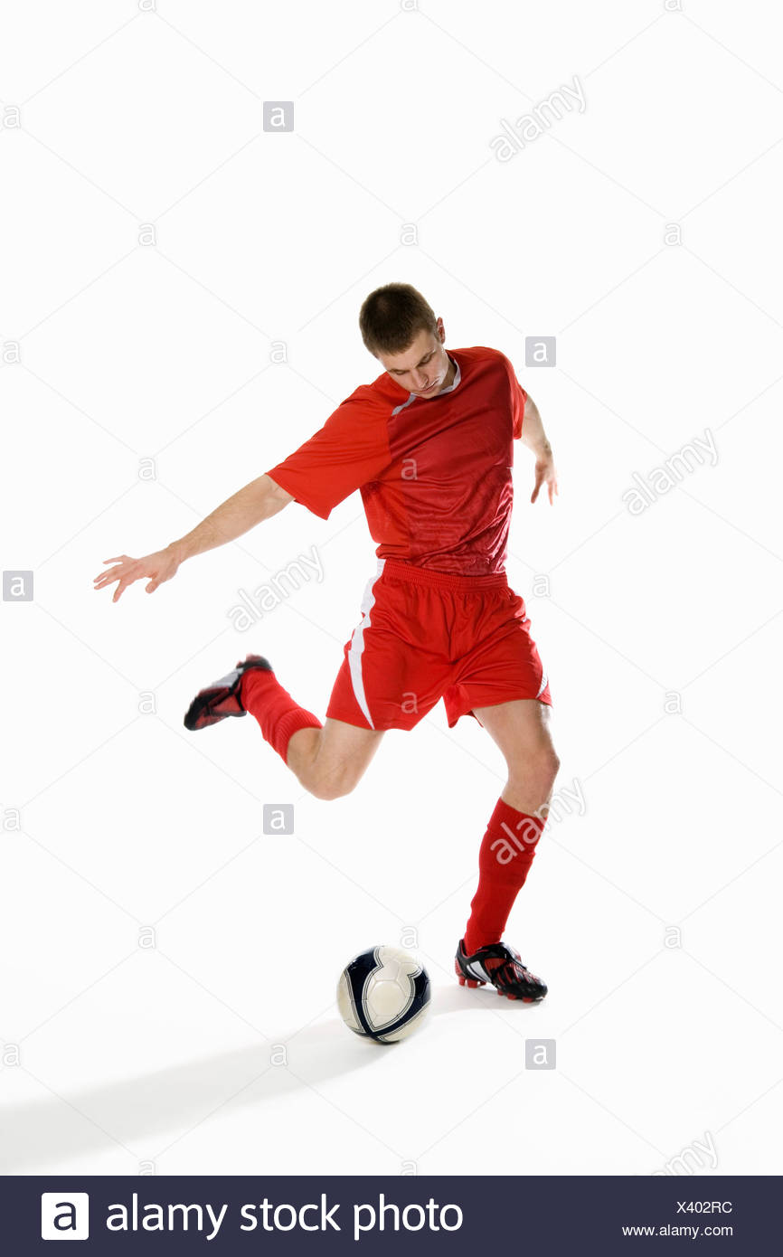 Studio shot of a soccer player kicking a soccer ball - Stock Image