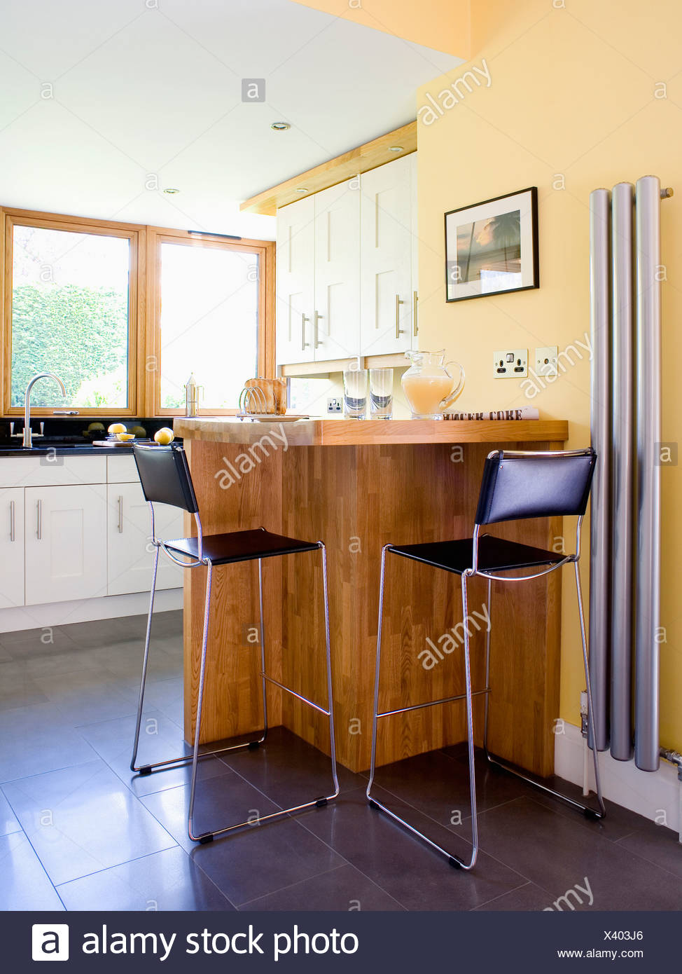 Black And Chrome Stools At Breakfast Bar In Modern Kitchen With Vertical Radiator On Wall Stock Photo Alamy