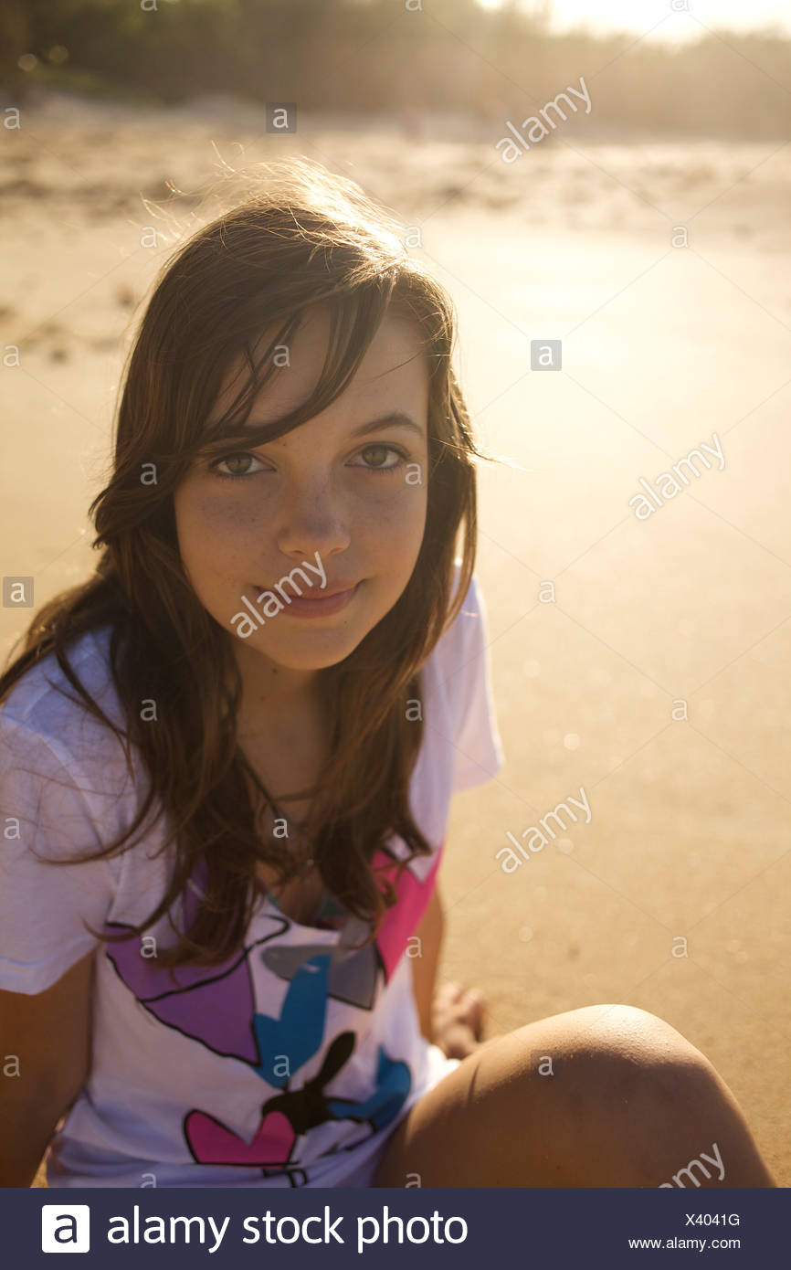 A pre-teen girl looks up at the camera and smiles at Paia Beach, Maui, Hawaii as the sun rises. - Stock Image