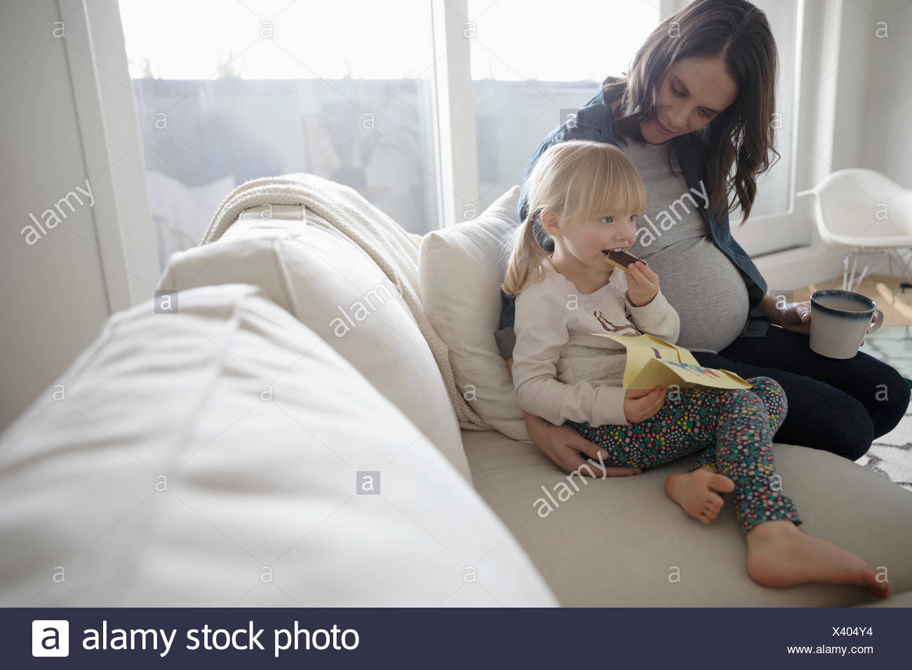 Pregnant mother and toddler daughter enjoying snack on living room sofa - Stock Image