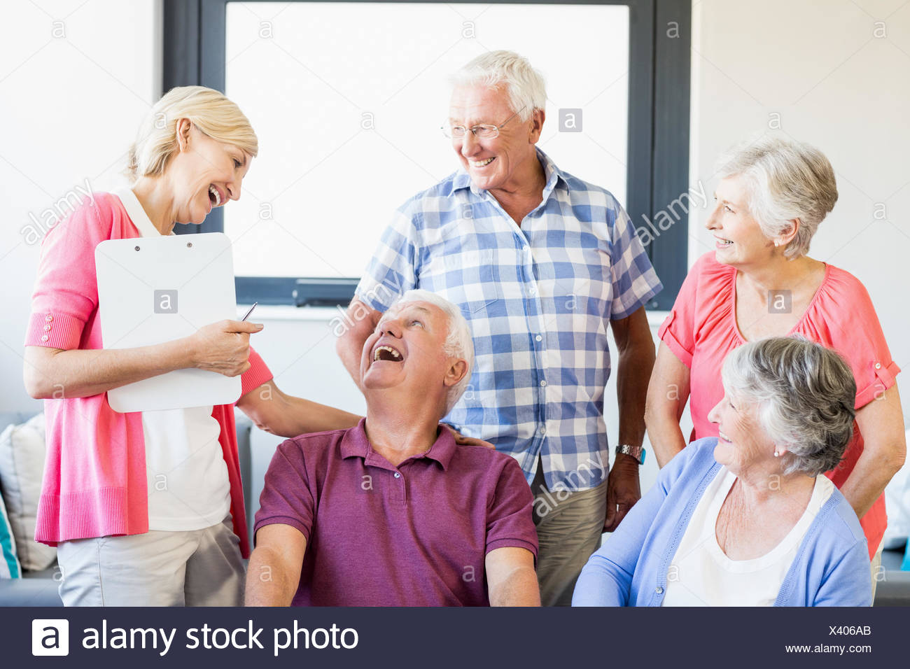 Seniors and nurse laughing together - Stock Image