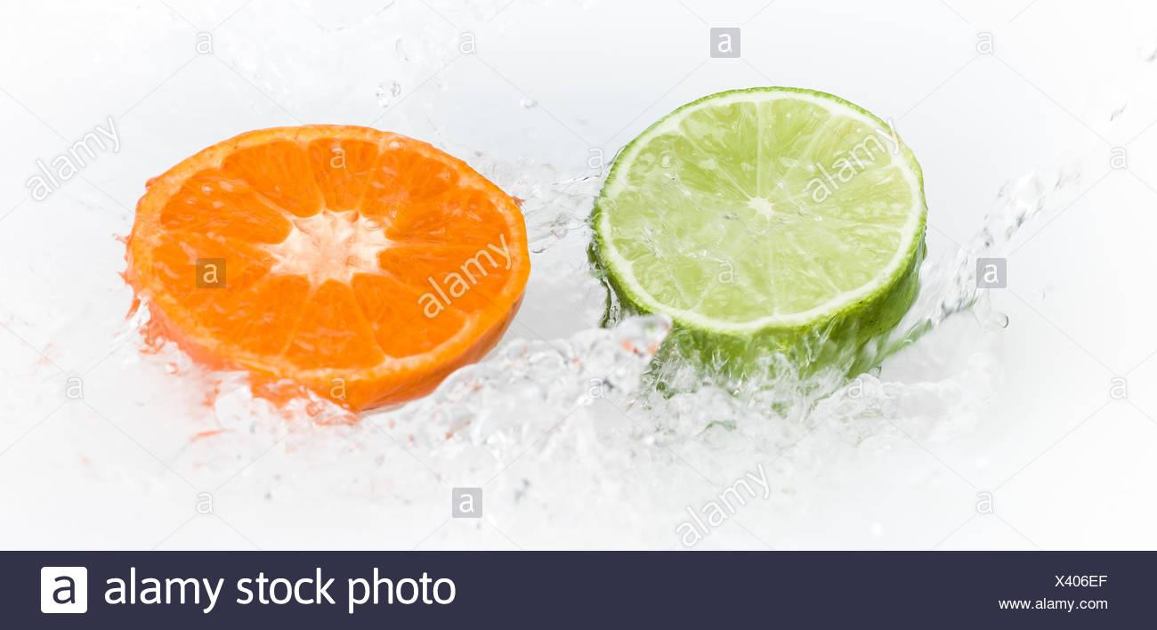 Water splashing bellow citrus fruit - Stock Image