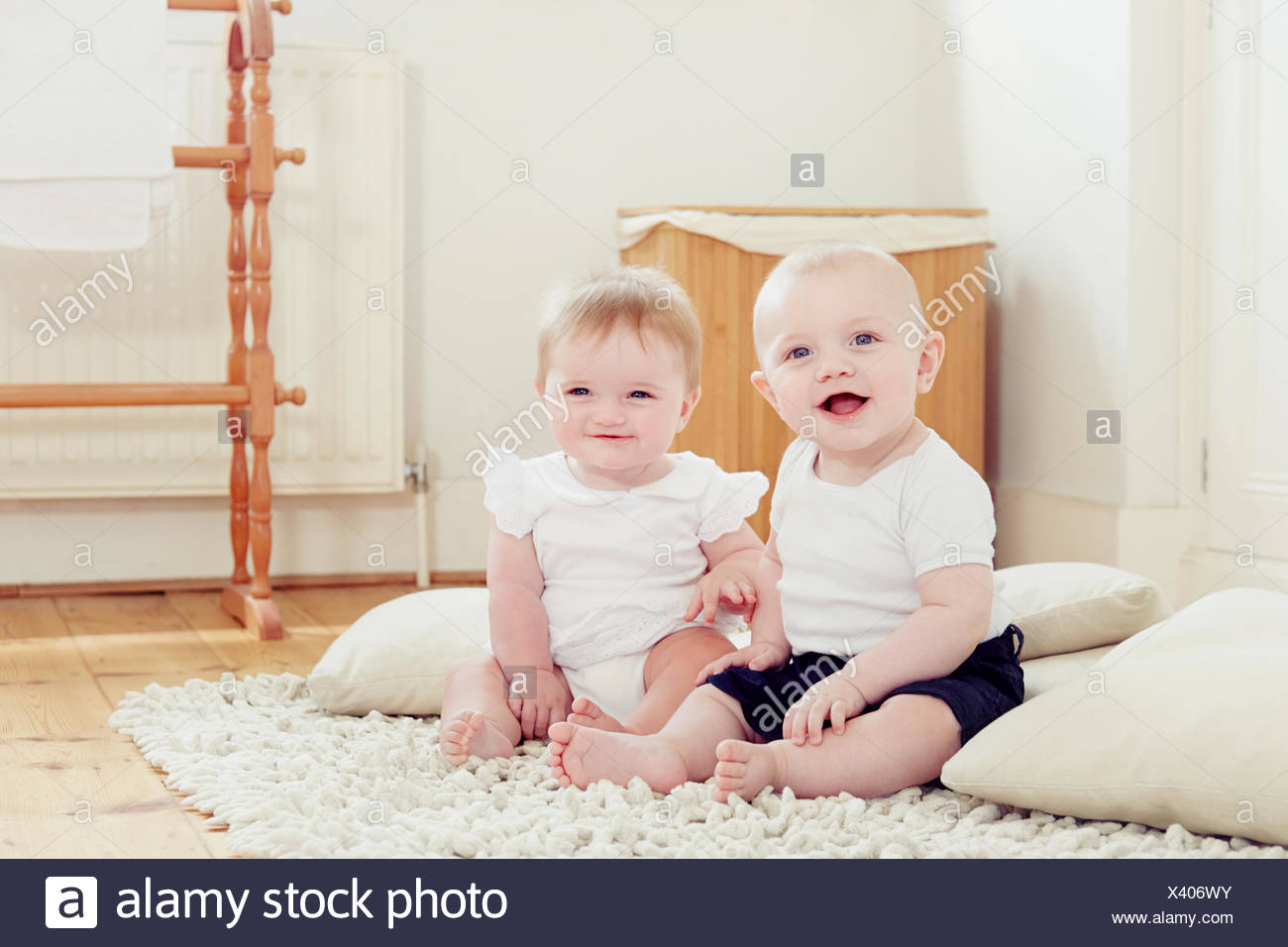 Portrait of smiling baby girl and baby boy sitting on rug - Stock Image