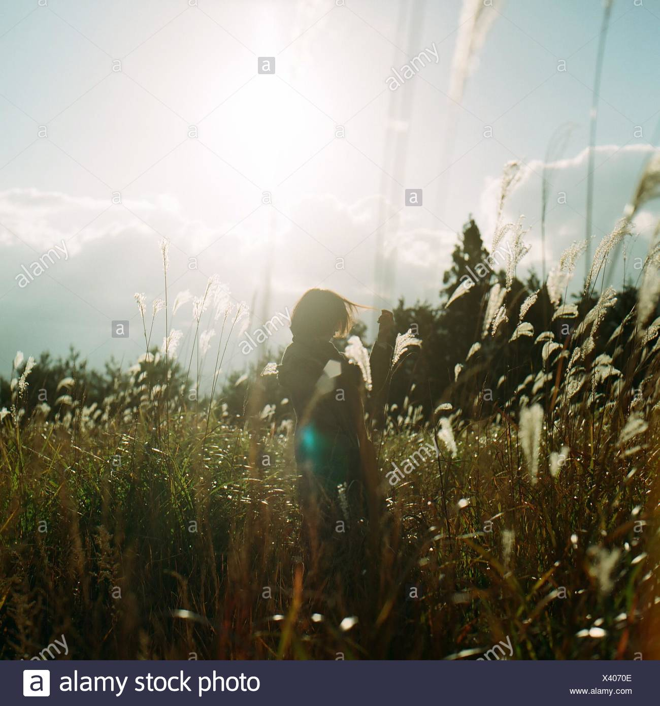 Woman Standing On Grassy Field Against Sky - Stock Image
