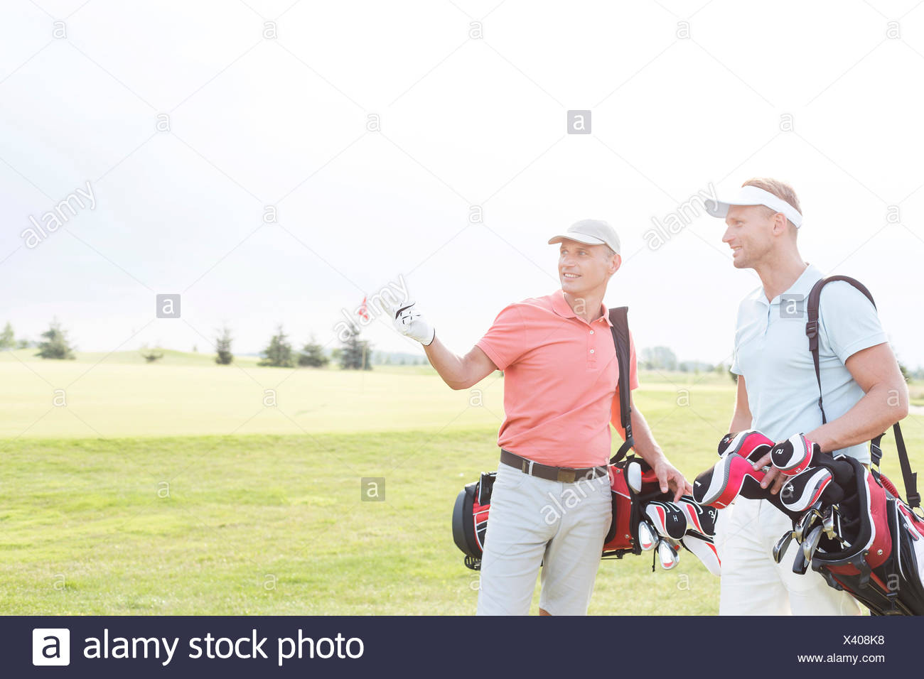 Man showing something to friend at golf course against clear sky - Stock Image