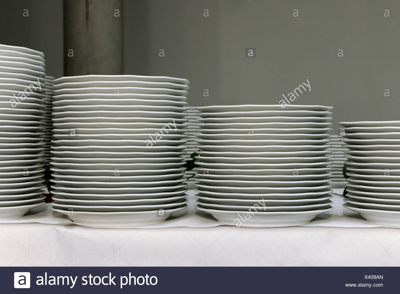 Stacks of white dinner plates on a table, preparations for a corporate event, Thuringia, Germany, Europe - Stock Image