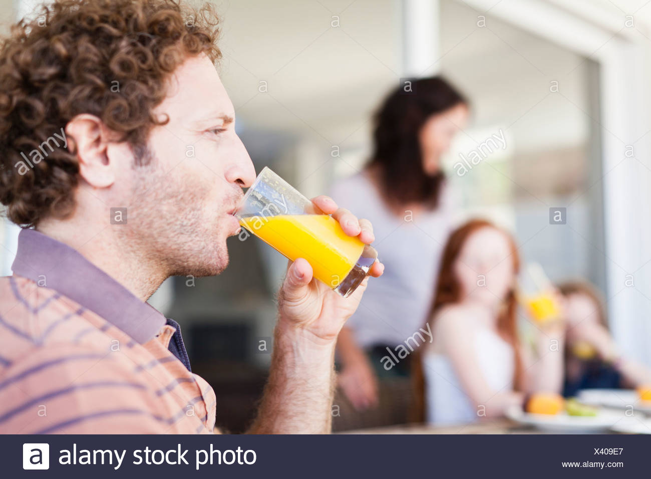 Man drinking glass of orange juice - Stock Image