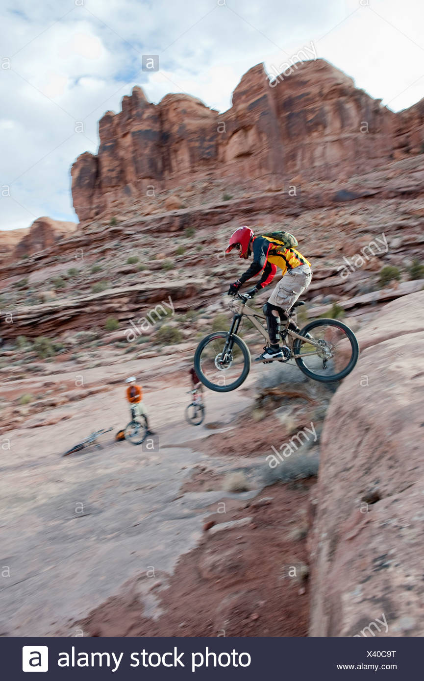 A downhill mountain biker launches off a drop on the Amasa Back Trail in Moab, UT. - Stock Image
