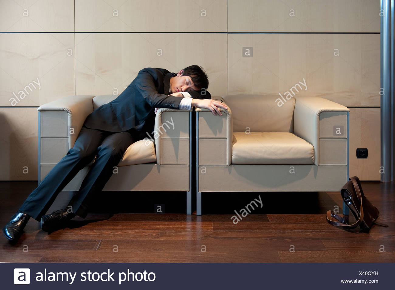 Chinese businessman sleeping in office - Stock Image