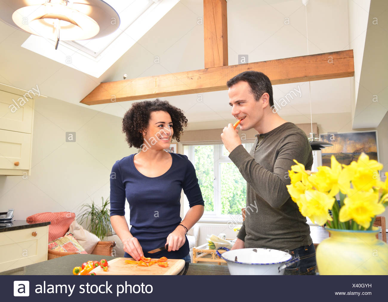 Couple in kitchen tasting and slicing peppers - Stock Image
