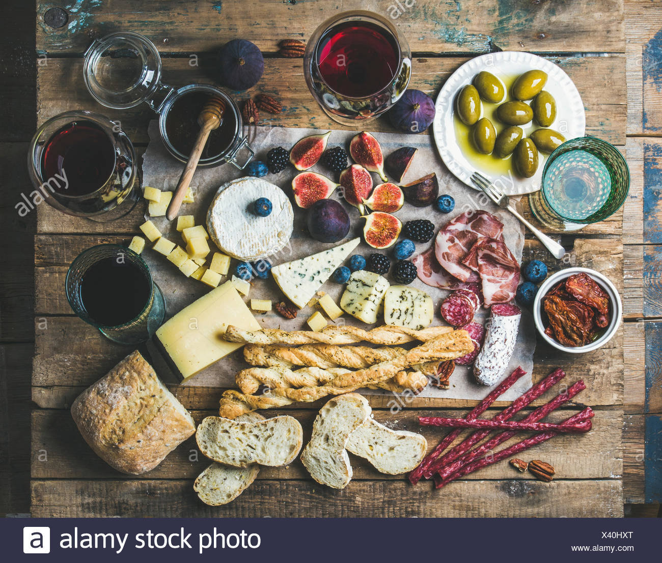 Wine and snack set with various wines in glasses, meat variety, bread, sun-dried tomatoes, honey, green olives, figs, nuts and b - Stock Image