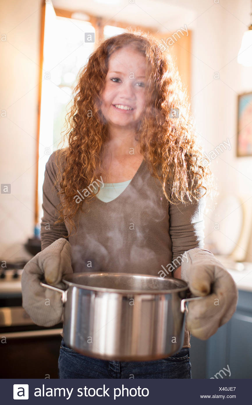 Teenage girl cooking in kitchen - Stock Image