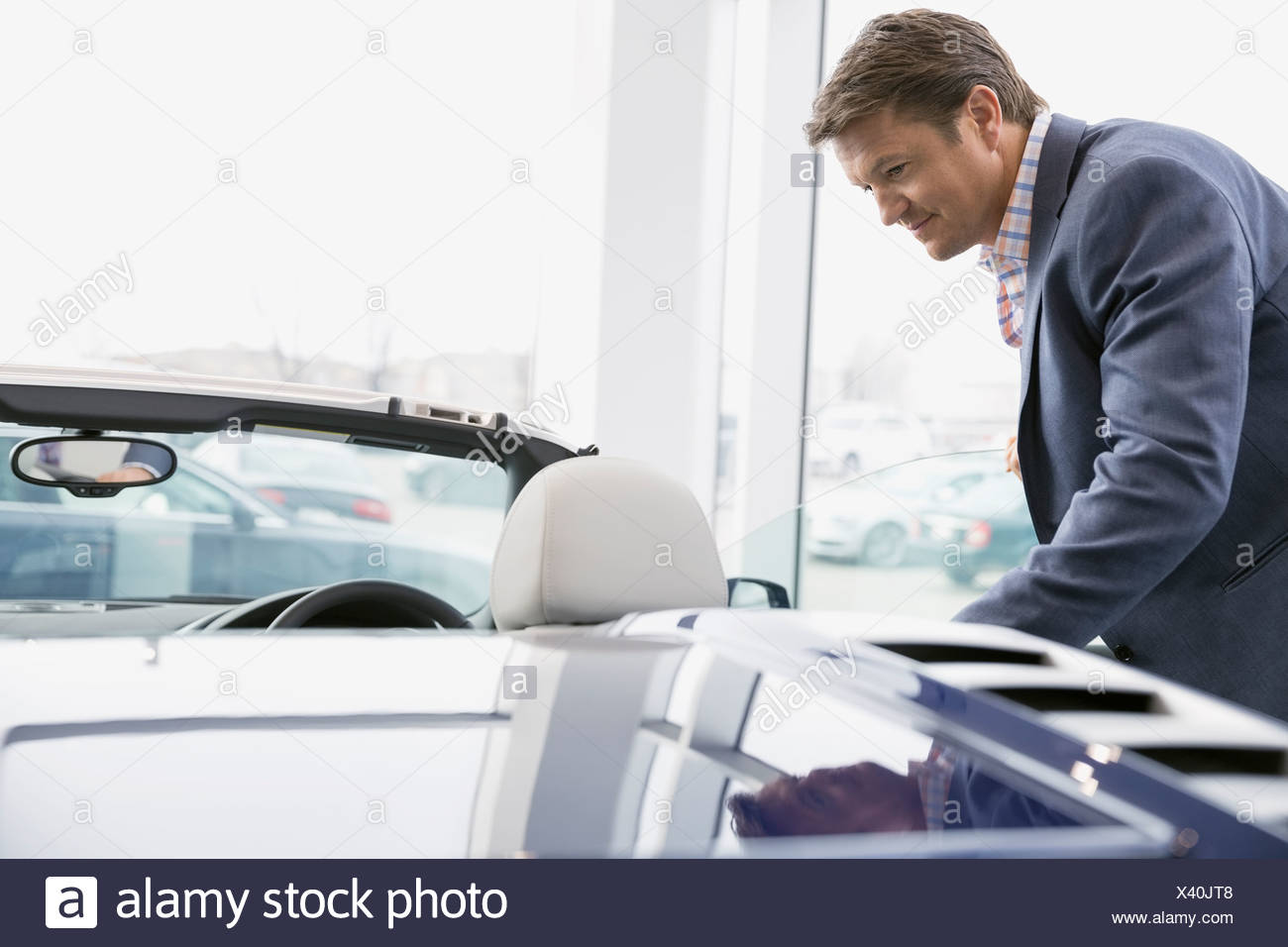 Man looking at convertible in car dealership showroom - Stock Image
