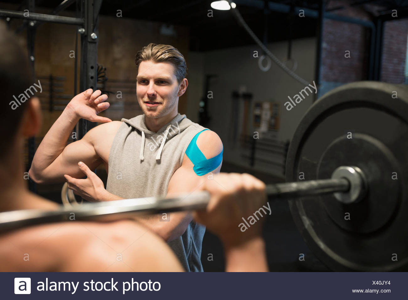 Personal trainer guiding man weightlifting barbell at gym - Stock Image