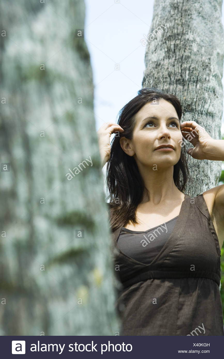 Woman leaning against tree trunk, pushing hair behind ears, looking up - Stock Image