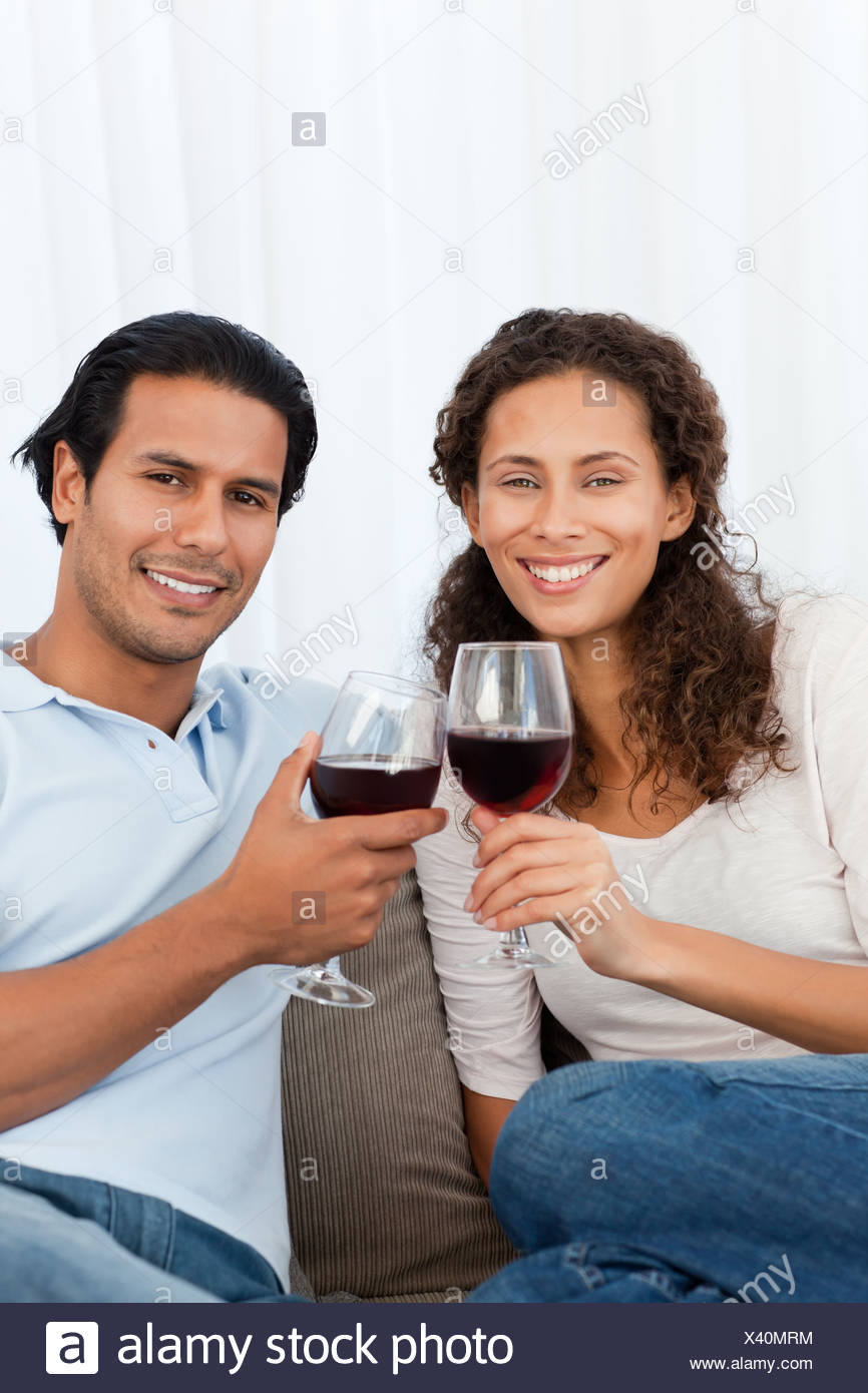 Happy couple clinking glasses of red wine on the sofa - Stock Image