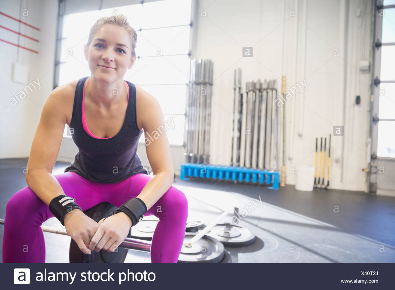 Portrait of confident woman sitting on barbell - Stock Image