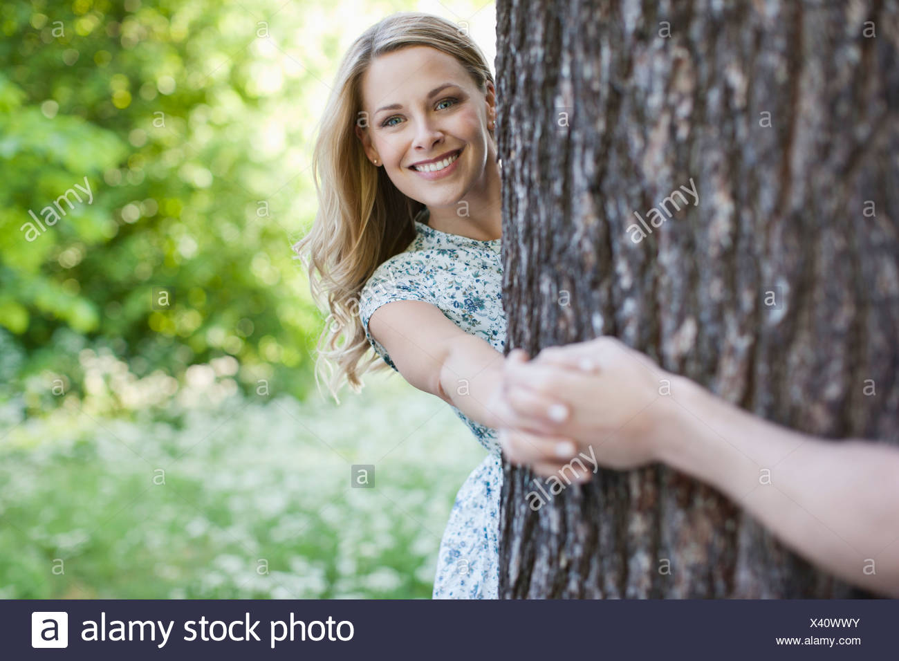 Couple holding hands around tree - Stock Image