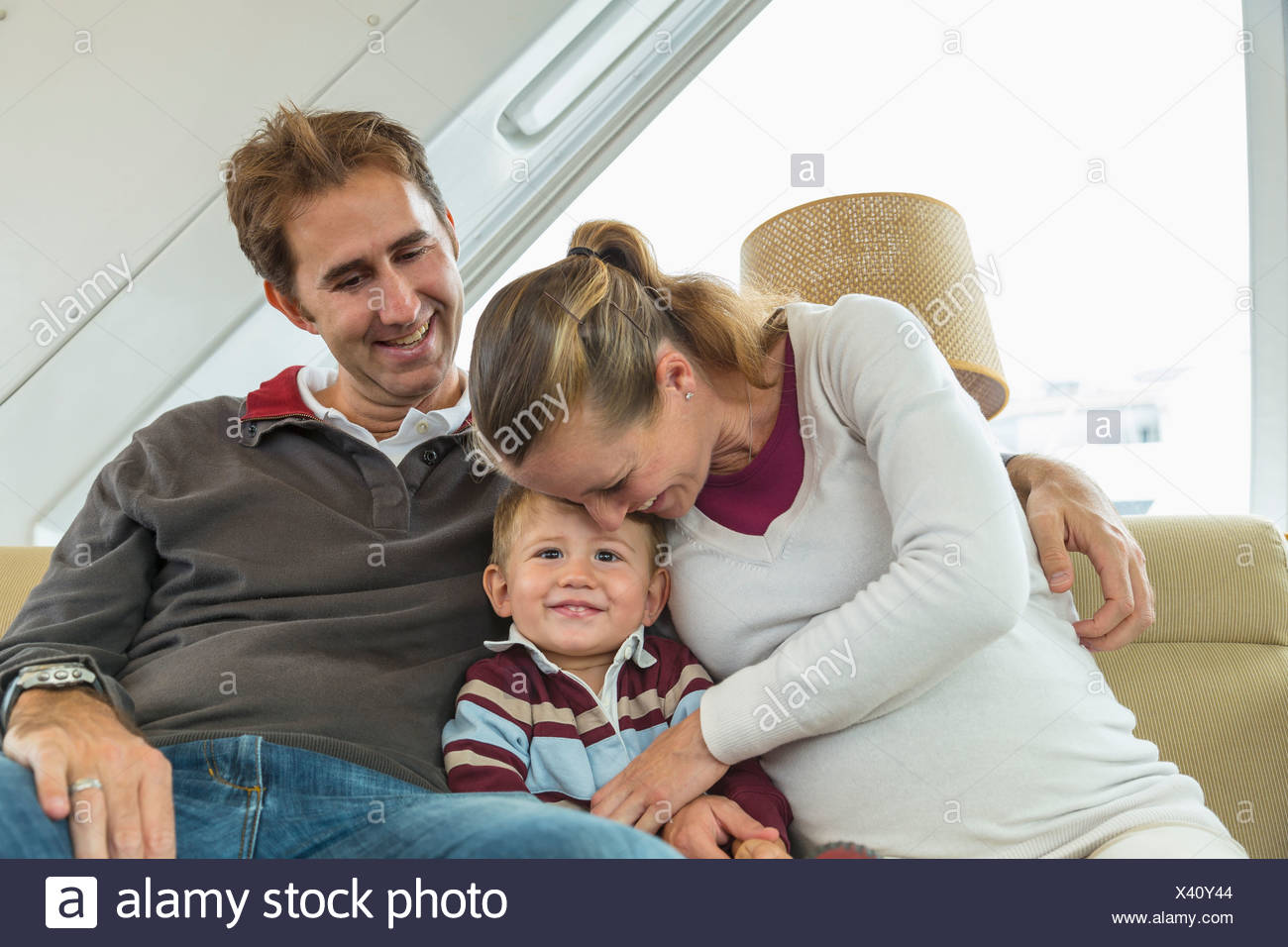 Mid adult couple and toddler son sitting on couch - Stock Image