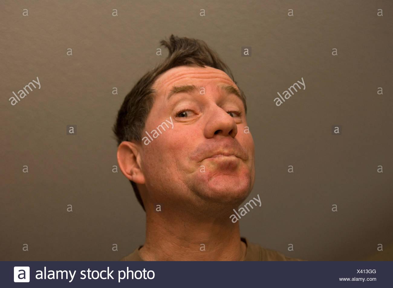 A man makes a goofy face. - Stock Image