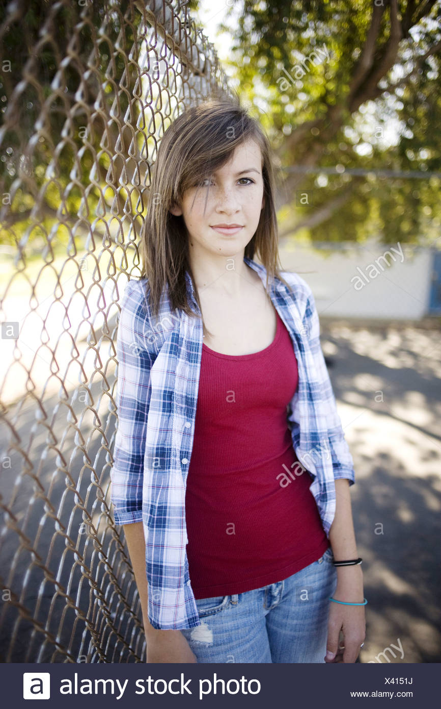 Girl leaning against chainlink fence - Stock Image