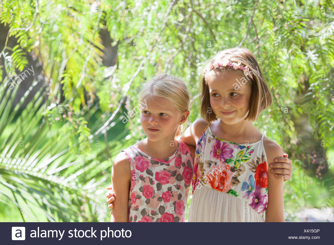 Candid portrait of two girls looking away in garden Stock Photo