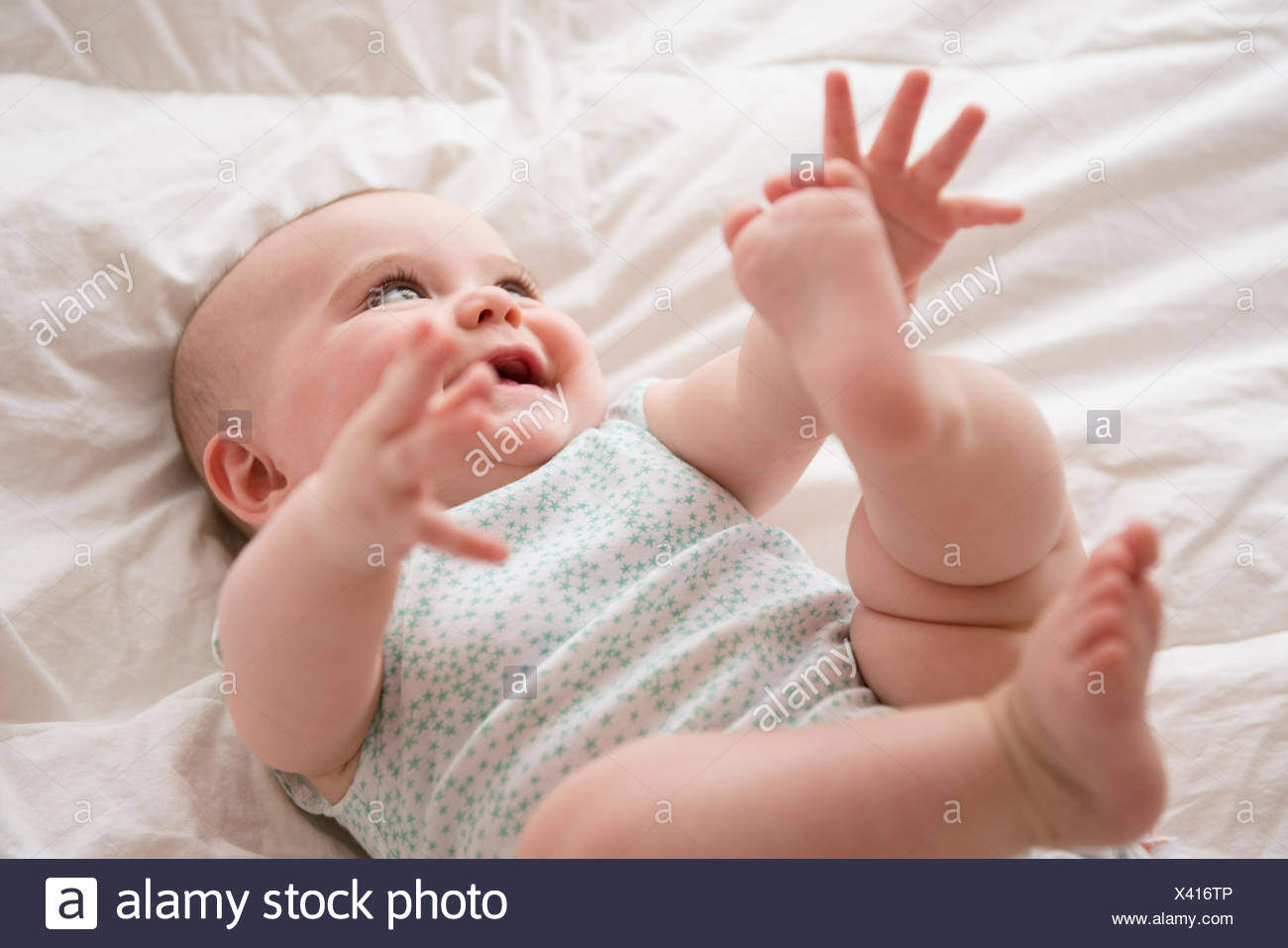 Baby girl (12-17 months) lying down with arms and legs up - Stock Image