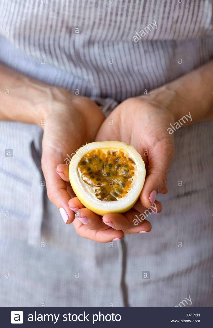 A woman holding half of a freshly cut passion fruit in her hands. Stock Photo