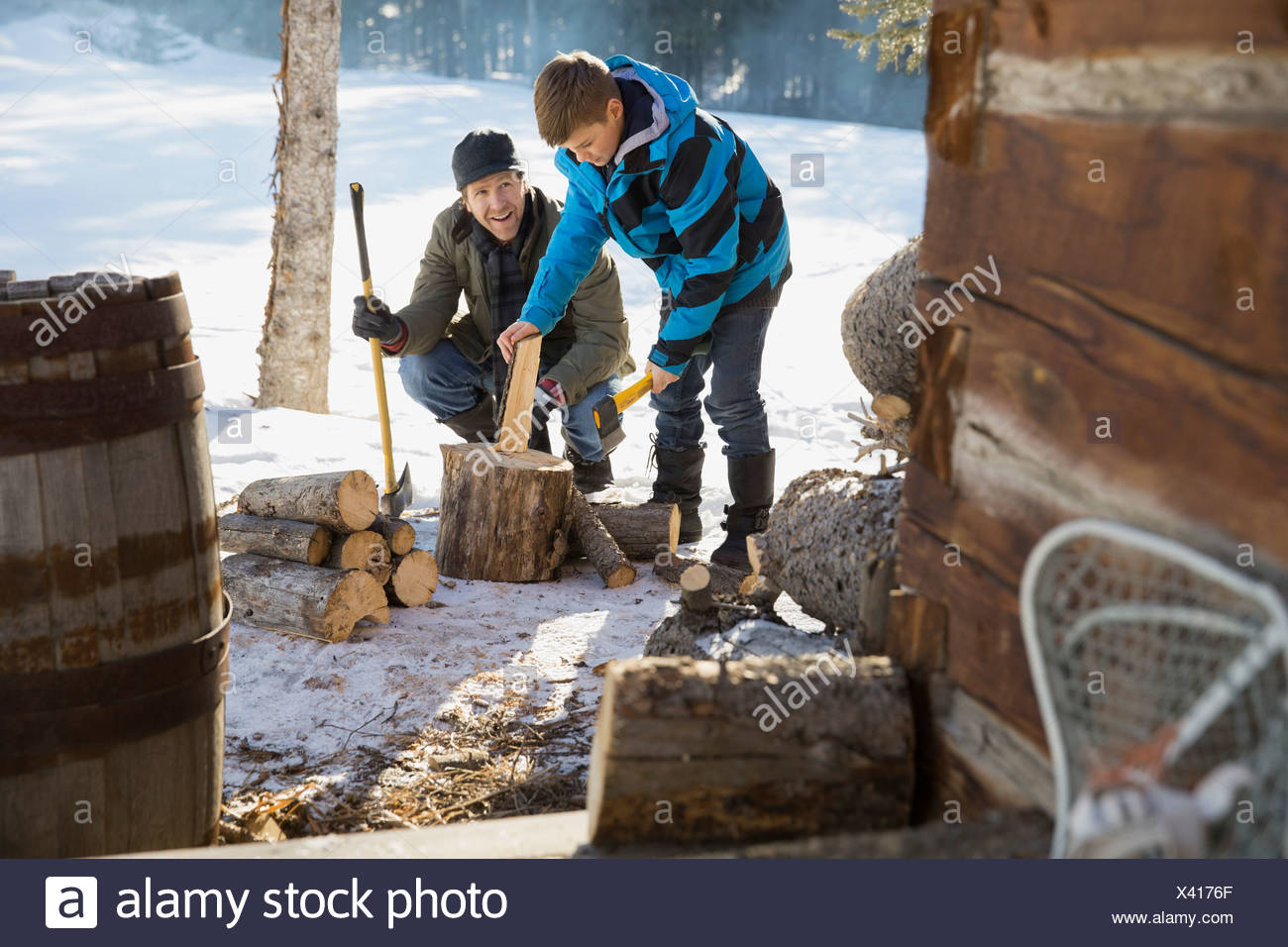 Father and son chopping firewood outside of log cabin - Stock Image