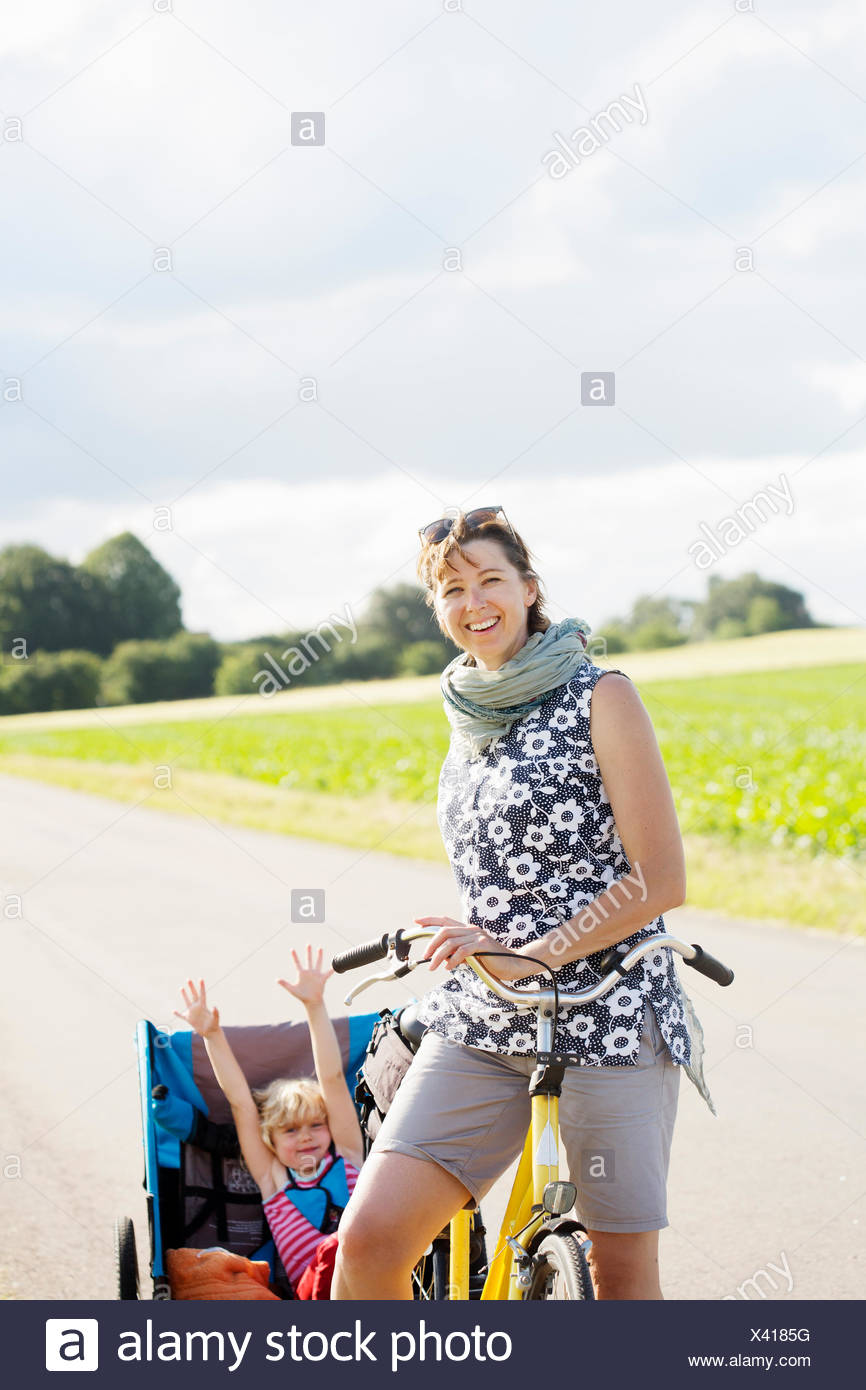 A mother cycling with her young daughter in a bicycle trailer - Stock Image