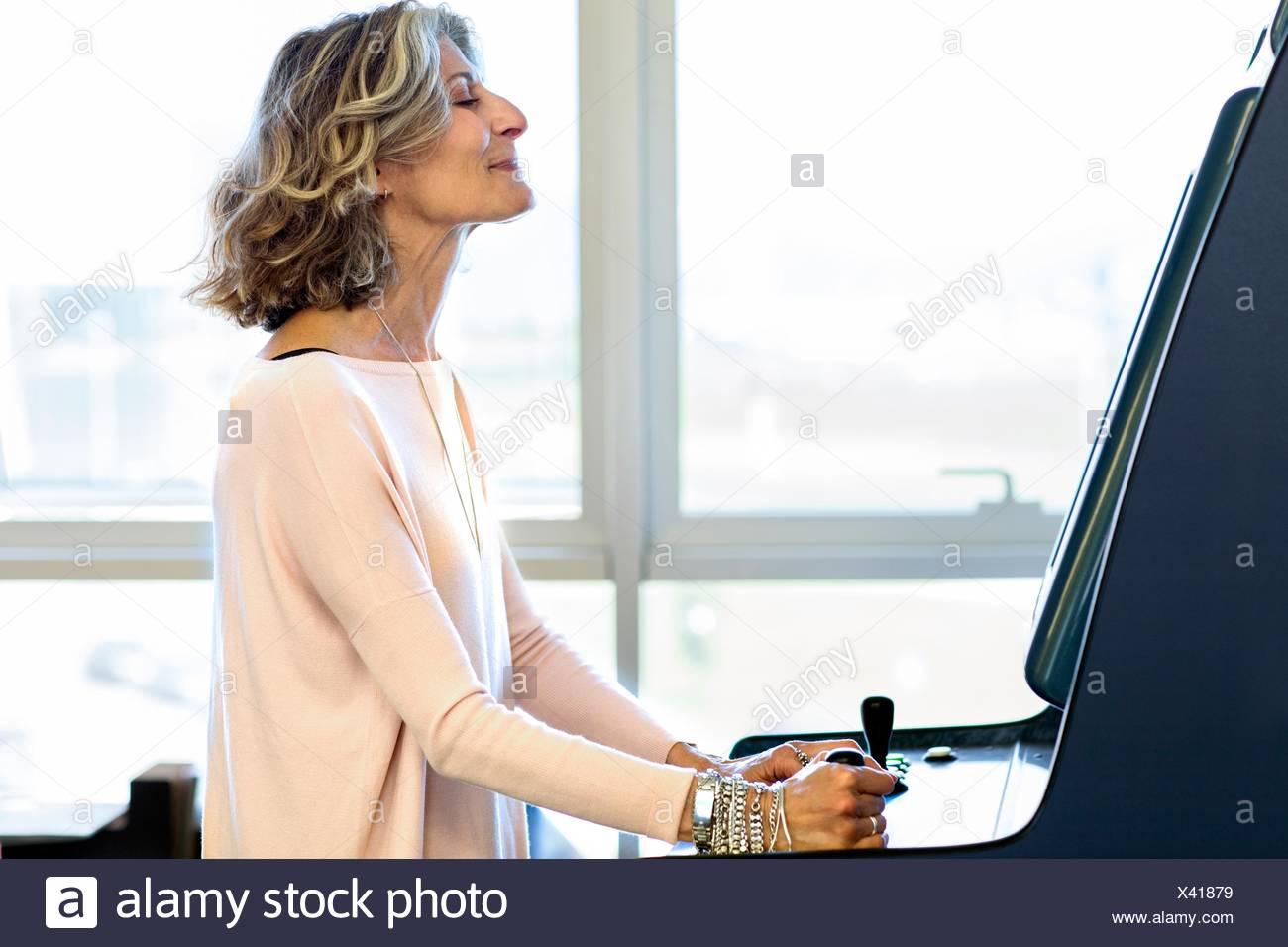 Senior female designer playing on games machine in office - Stock Image