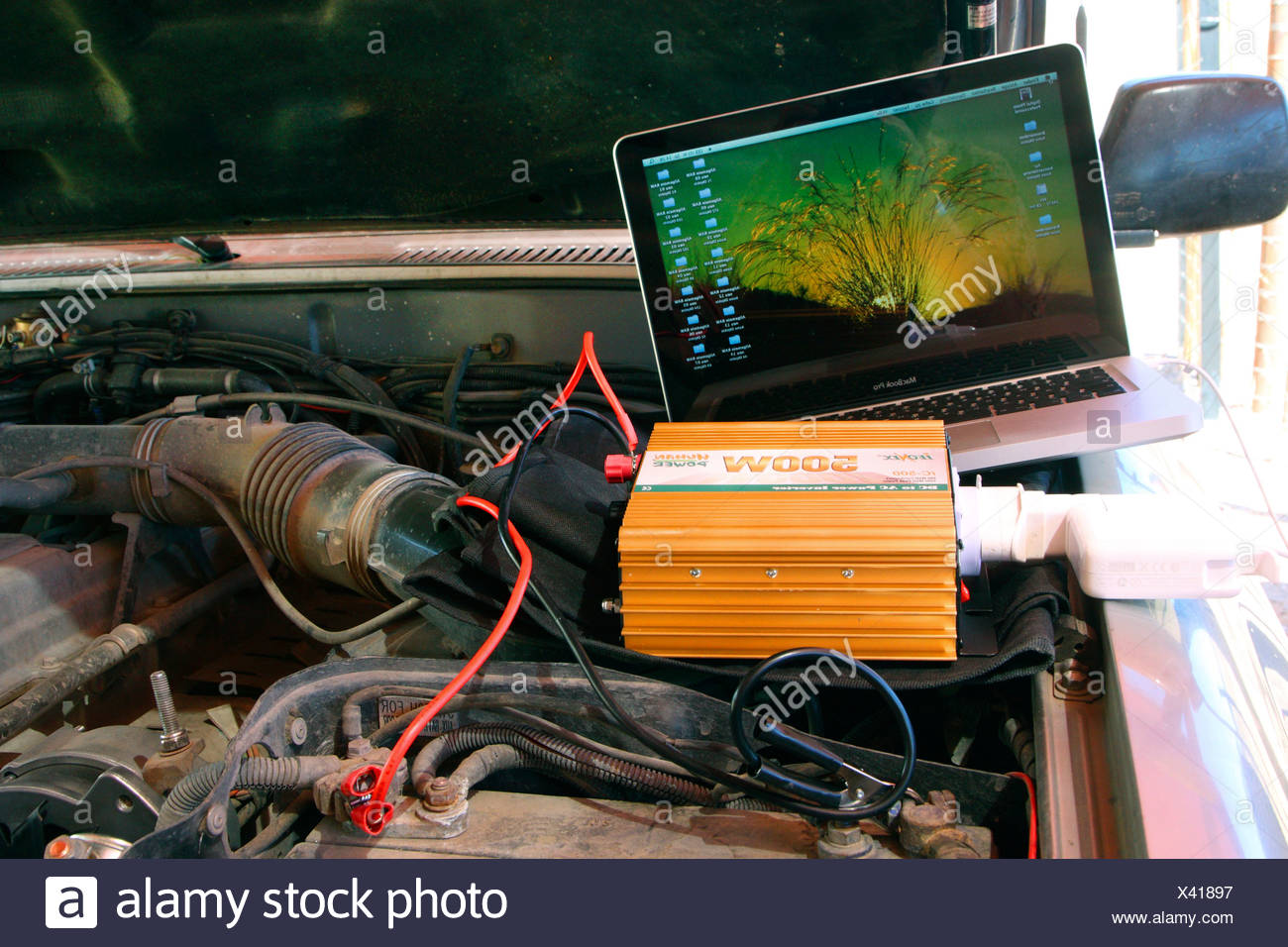 charging a laptop at a car battery in the Kalahari desert, South Africa - Stock Image
