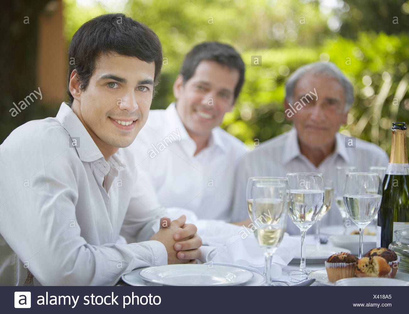 Man at outdoor party smiling with people in background - Stock Image