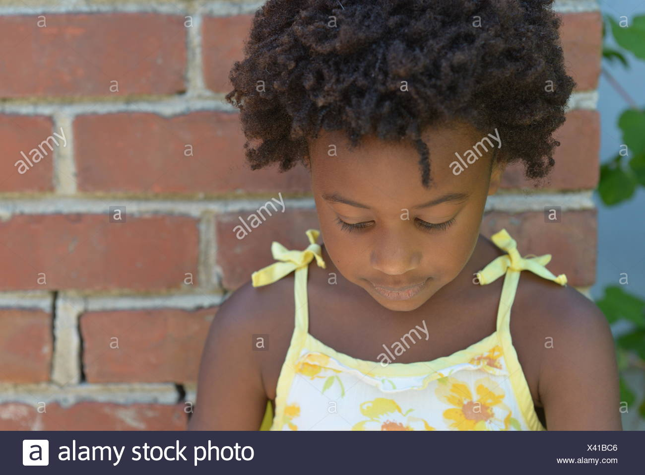 Girls standing by a brick wall looking down - Stock Image