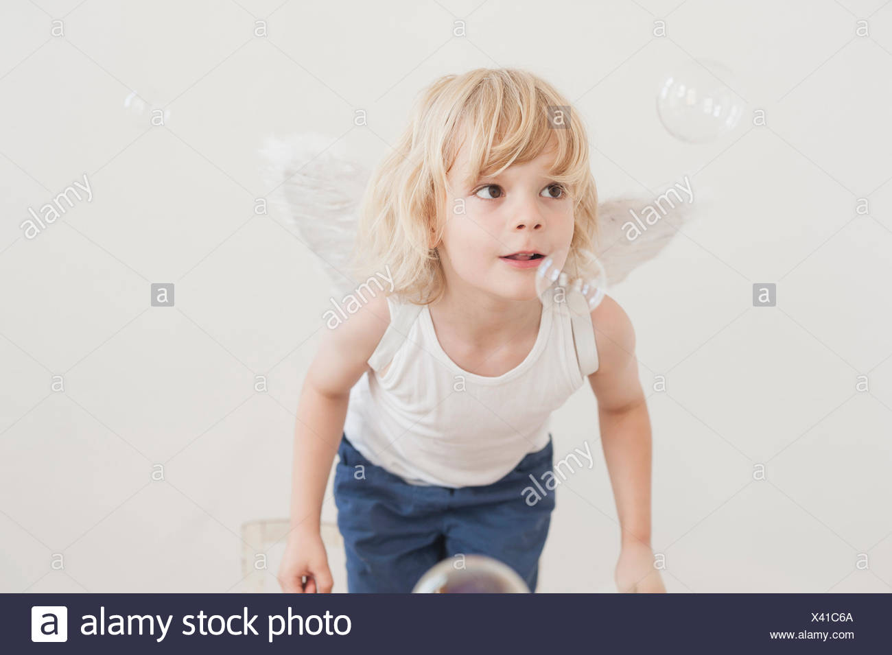 Portrait of little boy with angle wings watching soap bubbles - Stock Image